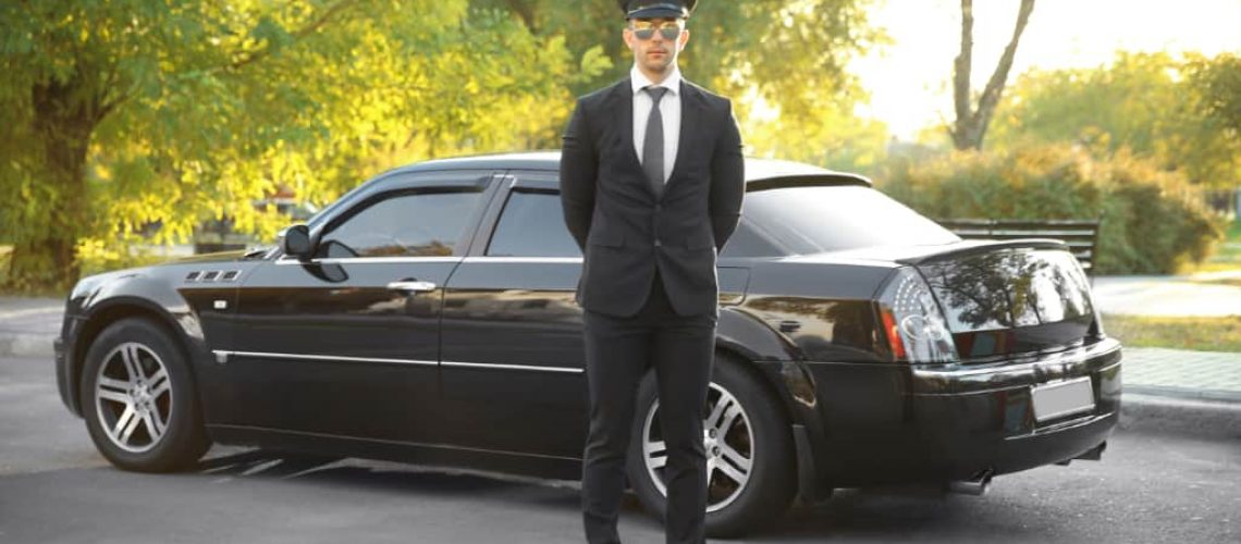 Young chauffeur standing near luxury car on the street
